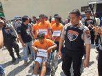 keterangan foto : para tersangka diapit oleh petugas kepolisian.